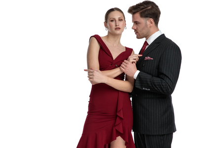Confident girlfriend looking to the camera and wearing a red dress while her boyfriend is holding her hand and wears a black suit, standing on white studio background