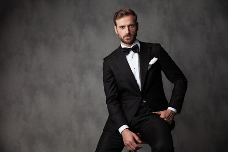 Serious looking young groom staring to the camera and holding on of his hands on his lag while wearing a black tuxedo on gray studio background Banco de Imagens