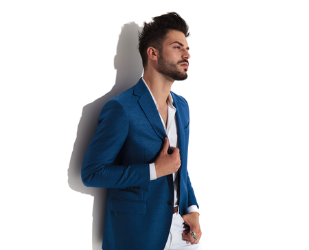 Sensual young man looking to the side and adjusting his jacket while holding on of his hand in his pocket and wearing a blue suit, leaning on white studio background Banco de Imagens