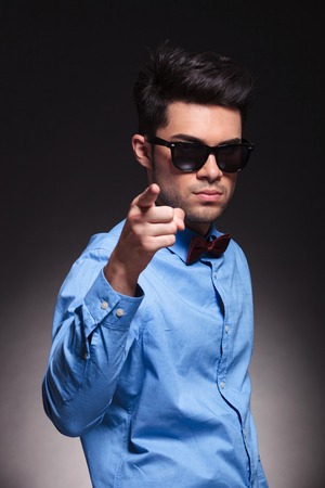 Serious looking young male pointing at the camera and standing while wearing sunglasses and suit on grey studio background