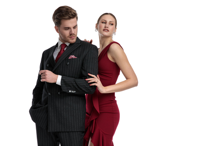 Mystified couple looking to the side, wearing a black suit and a red dress while the girlfriend is hugging her man from behind standing on white studio background