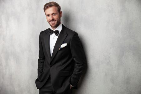 Positiver junger Mann, der lächelt und in die Kamera schaut, während er beide Hände in seinen Taschen hält und sich auf grauen Studiohintergrund stützt