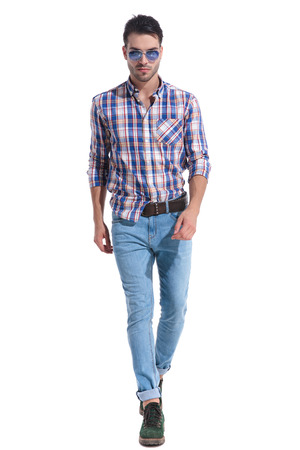 Determined man walking and looking straight to the camera while wearing sunglasses, a checkered shirt and blue jeans on white studio background