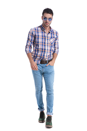 Confident guy walking forward and holding on of his hand in his pocket while wearing a pair of sunglasses and a checkered shirt on white studio background Stock Photo