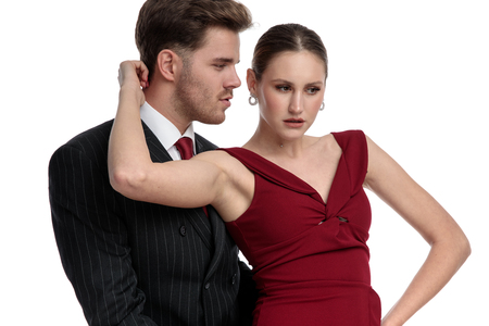 Sensual couple dressed in a black suit and red dress holding each other while he is looking at her and she is straing to the side, stranding on white studio background