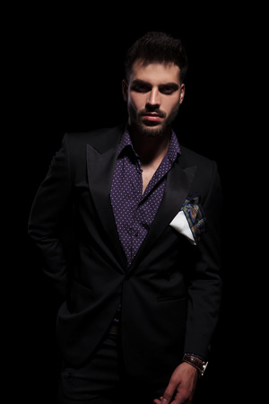 Serious looking guy confidently staring at the camera and reaching for his back pocket while wearing a black suit and standing on black studio background Banco de Imagens