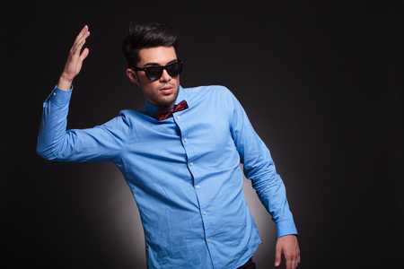 Angry guy standing and holding his arm in the air while looking sideways and wearing sunglasses and suit on gray studio background
