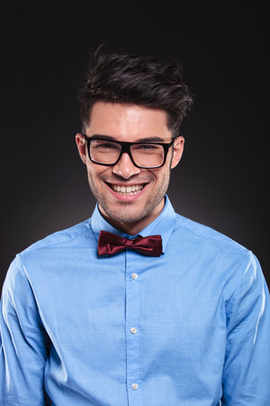 Happy looking guy standing, wearing glasses and suit while smiling and looking forward on grey studio background