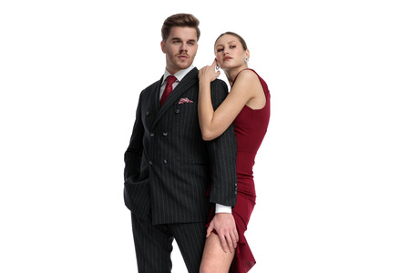 Romantic couple curiously looking to the side being dressed elegant while the man is holding one hand in his pocket and the other on the girl's leg who is wearing a red dress and is holding him from behind, standing on white studio background