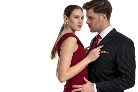 Passionate couple holding each other while the girl wearing a red dress is looking at the camera and the man dressed with a black suit romaticaly stares at her, on white studio background