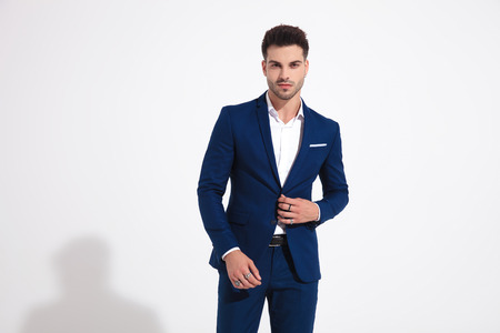 Charming man romantically staring to the camera and adjusting his jacket while wearing rings and a blue suit on white studio background