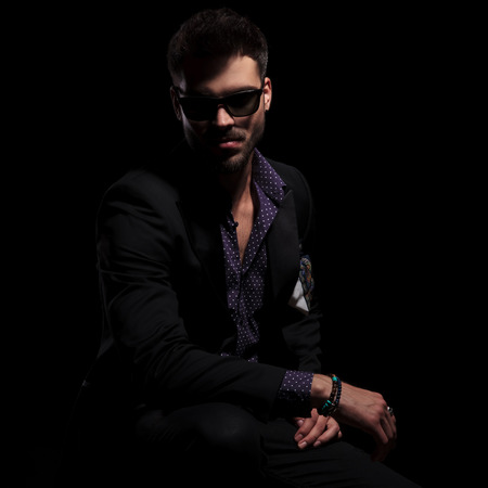 Serious looking guy staring to the camera and wearing a black suit and sunglasses while resting his arms on his legs and sitting on black studio background