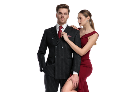 Handsome guy dressed with a black suit and holding one hand in his pocket get his tie fixed by his girlfriend wearing a red suit and looking at him, standing on white studio background