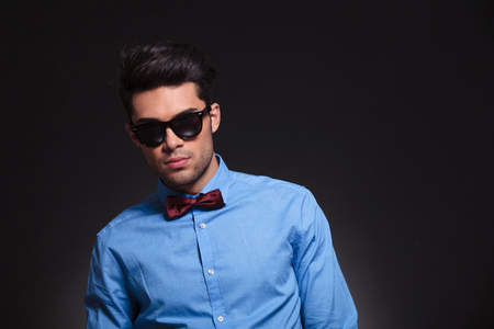Serious looking young male standing and staring forward while wearing sunglasses and suit on grey studio background