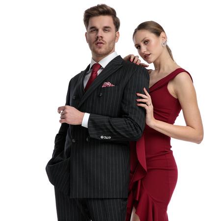 Pareja segura mirando a la cámara y vestida elegante mientras la chica sostiene a su novio por detrás, de pie sobre fondo blanco de estudio Foto de archivo