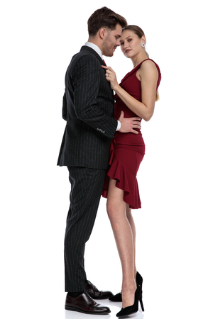 Romantic young guy dressed with a black suit holding his girlfriend by the hips while she is adjusting his jacket and is wearing a red dress, stranding on white studio background
