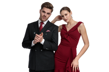 Confident you man dressed in a black suit rubbing his hand while his girlfriend wearing a red dress is posing next to him, looking at the camera and standing on white studio background Stockfoto
