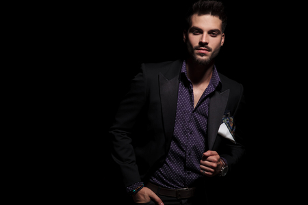 Serious looking man staring straight to the camera and holding one of his hands in his pocket while fixing his jacket and standing on black studio background Stockfoto