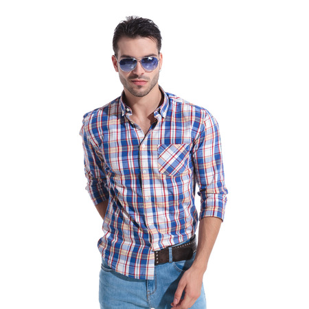 Confident young man looking the camera and reaching for his back pocket while wearing a pair of sunglasses and a checkered shirt, standing on white studio background