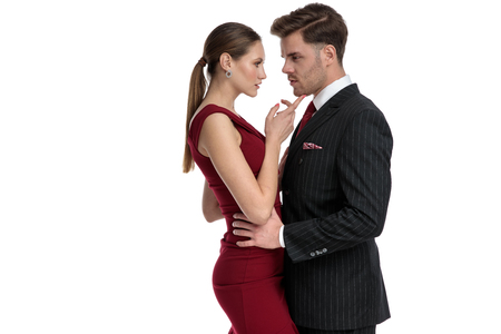 Beautiful girl wearing a red dress and holding one of her arms on her boyfriend chest, touching his chin with the other hand, while the man dressed in a black suit is holding her by the hips, on white studio background Imagens