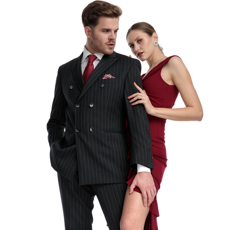 Determined man wearing a black suit, holding one of his hand in his pocket and one on his girlfriend's legs while she is wearing a red dress and is touching his arm, standing on white studio background Stockfoto