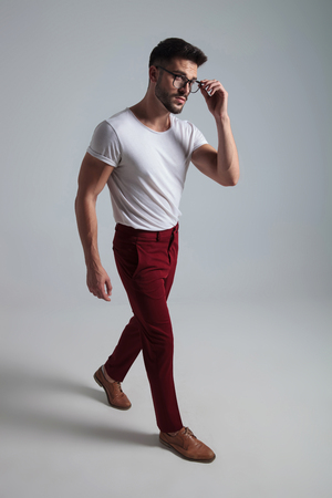 Curious man walking to the side and adjusting his glasses while wearing a white t-shirt and red pants on gray studio background