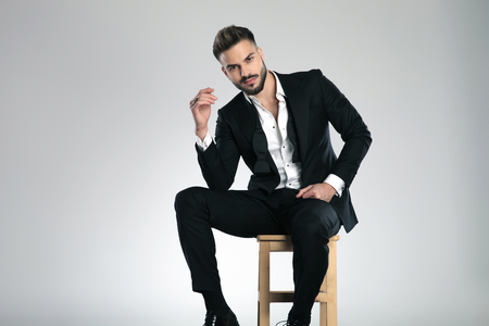 Determined guy looking to the camera and holding his hand in the air while wearing a black tuxedo and sitting on gray studio background