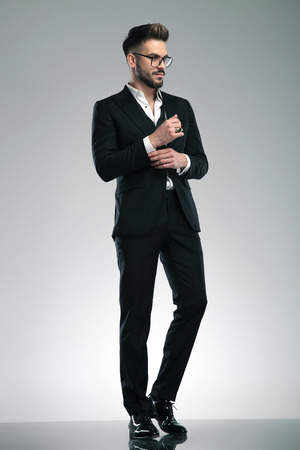 Mystified young man adjusting his sleeve and looking to the side while wearing glasses and a black tuxedo, standing on gray studio background