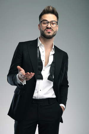 Indifferent guy gesturing and holding his hand in his pocket while wearing a black tuxedo and glasses, standing on gray studio background