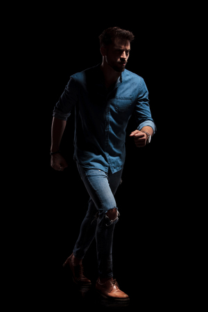 Serious looking guy walking hurried to the side with his fist clenched while wearing a blue shirt and jeans on black studio background