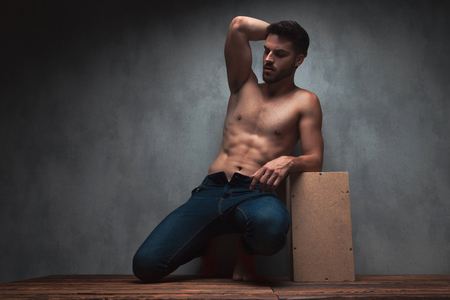 Sensual young guy kneeing and holding one of his hands on his head while wearing only jeans and leaning on a box, on gray studio background Imagens