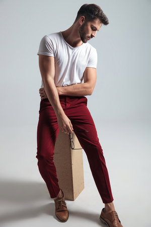 Concerned man holding his glasses and looking downwards while wearing a white t-shirt and red pants, sitting on gray studio background Stockfoto - 123096506