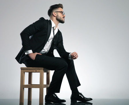 Concerned young man looking to the side and sitting while wearing a black tuxedo and glasses and holding his hand in his pocket on gray studio background
