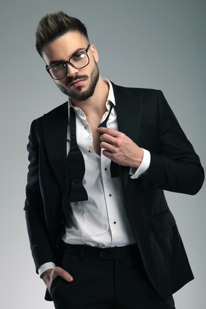 Sexy young man adjusting his untied bowtie and holding his hand in his pocket while looking to the camera and wearing glasses and black tuxedo, standing on gray studio background