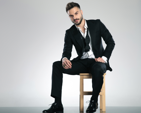 Serious looking guy staring to the camera and wearing a black tuxedo while sitting on a chair on gray studio background