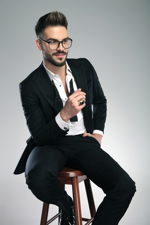 Positive guy looking to the side and holding his hand in his pocket while wearing glasses and a black tuxedo, sitting on gray studio background