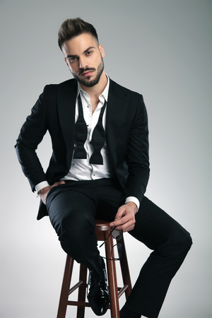 Attractive guy holding his glasses and one hand in his pocket while wearing a black tuxedo and looking to the camera, sitting on gray studio background Banco de Imagens