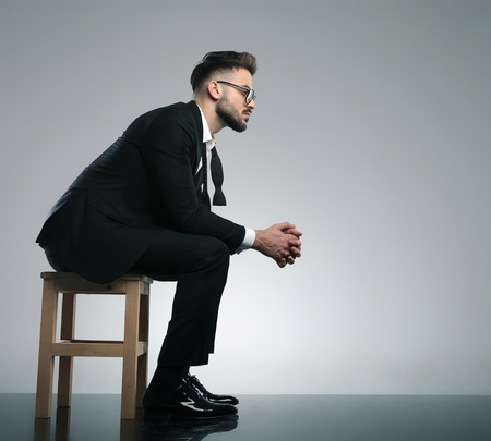 Side view of a thoughtful man looking forward with his hand clenched while wearing a black tuxedo and glasses, sitting on gray studio background
