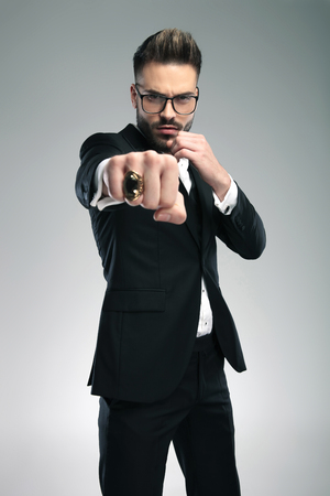 Tough guy standing in a fighting pose with his fist clenched and ring showing while wearing glasses and a black tuxedo on gray studio background