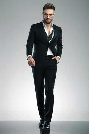 Confident guy stepping forward and holding his hand in his pocket while wearing glasses and a black tuxedo on gray studio background Stock Photo