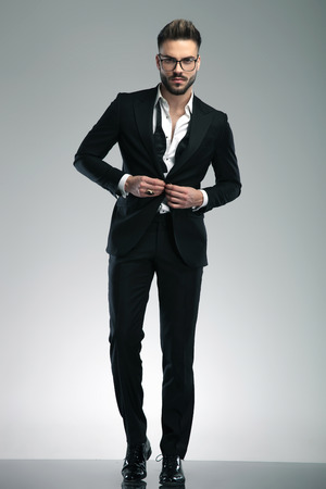 Confident guy fixing his jacket and looking to the camera while wearing glasses and a black tuxedo, stepping on gray studio background