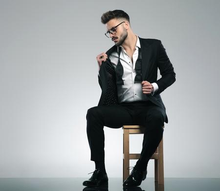 Ragazzo sexy che si aggiusta la giacca e guarda di lato mentre indossa gli occhiali e uno smoking nero, seduto su uno sfondo grigio dello studio