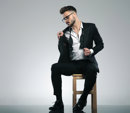 Sexy guy adjusting his jacket and looking to the side while wearing glasses and a black tuxedo, sitting on gray studio background