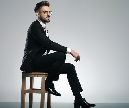Concerned guy looking to the side while wearing a black tuxedo and glasses, sitting on a chair on gray studio background