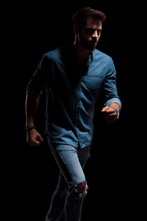Brave man running to the side while wearing a blue shirt and jeans with a light shade hitting him on black studio background Banco de Imagens