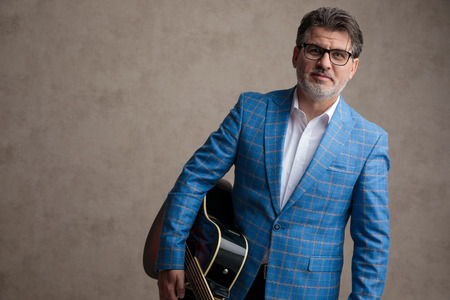 Positive businessman holding his guitar and smiling to the camera while wearing glasses and a blue suit on gray wallpaper background