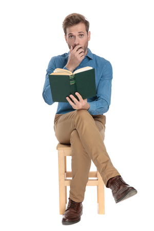 Astonished young man holding a book and his hand in front of his mouth while wearing a blue shirt and brown pants, sitting with his legs crossed on white studio background