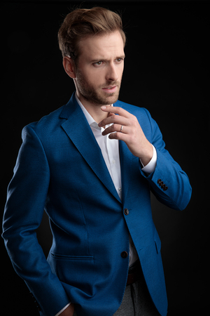 Concerned young man holding his hand in his pocket and looking to the side with his arms around his chin while wearing a blue suit and standing on black studio background