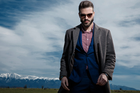 Powerful businessman posing and looking to the camera while wearing sunglasses, a blue suit and gray coat, standing on outdoor background Banco de Imagens