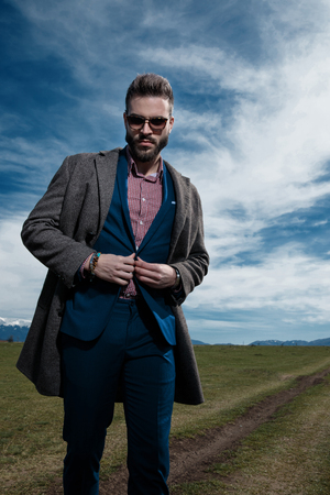 Determined man walking and closing his jacket's buttons while wearing a gray coat, blue suit and sunglasses on outdoor background Banque d'images